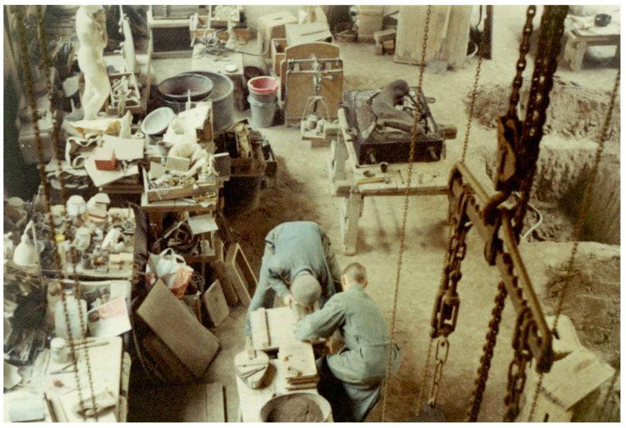 Färgbild ur gjuteriets senare historia. Ur Otto Meyers arkiv hos Centrum för Näringslivshistoria. Till höger syns en grop där de nyss gjutna statyerna kunde grävas ner för avsvalning.