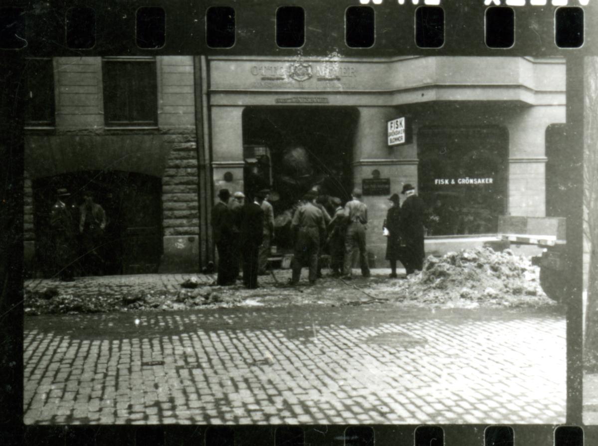 """Statyn """"Timmerflottarna"""" forslas genom porten ut mot gatan ca 1940. Ur Otto Meyers arkiv hos Centrum för Näringslivshistoria."""